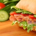 Fresh ham sandwich on wooden board — Stock Photo #15687047