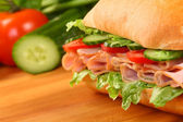 Fresh ham sandwich on wooden board — Stock Photo