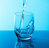 Water poured into glass. Toned in blue — Stock Photo