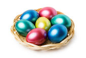 Multi-colored Easter eggs in basket — Stock fotografie