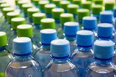 Many bottles of clean water with blue and green lids — Stock Photo