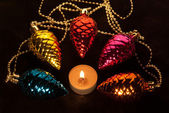 Burning candle and garland from glass cones on fur — Stock Photo