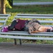 Homeless elderly woman sleeps on bench in Park — Stock Photo