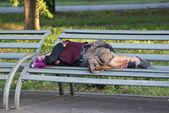 Homeless elderly woman sleeps on bench in Park — Stock Photo