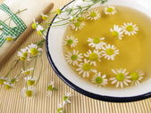 Bath essence with chamomile flowers — Stock Photo