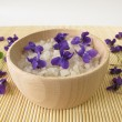 Bath salt with violet flowers — Stock Photo