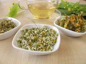 Cup of tea and dried chamomile flowers, elderflowers and linden flowers — Stock Photo