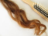 Genuine auburn hair strand and a hairbrush — Stock Photo