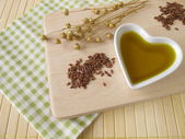 Linseed oil in a small heart-shaped porcelain bowl — Stock Photo