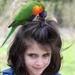 Girl and rainbow lorikeet — Stock Photo