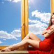 Beautiful lady sitting on window — Stock Photo