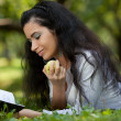 The girl with an apple and the book on a grass — Stock Photo