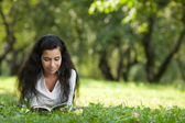 The girl on a grass reads the book — Stock Photo