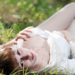 The woman on a grass in a white shirt — Stock Photo #16794457