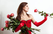 The woman in a red corset holds roses — Stock Photo