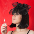 The woman with a cigaret in a black hat — Stock Photo