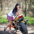 Foto Stock: Girl is standing next to motorcycle