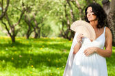 A woman in the park holds a fan — Stock Photo