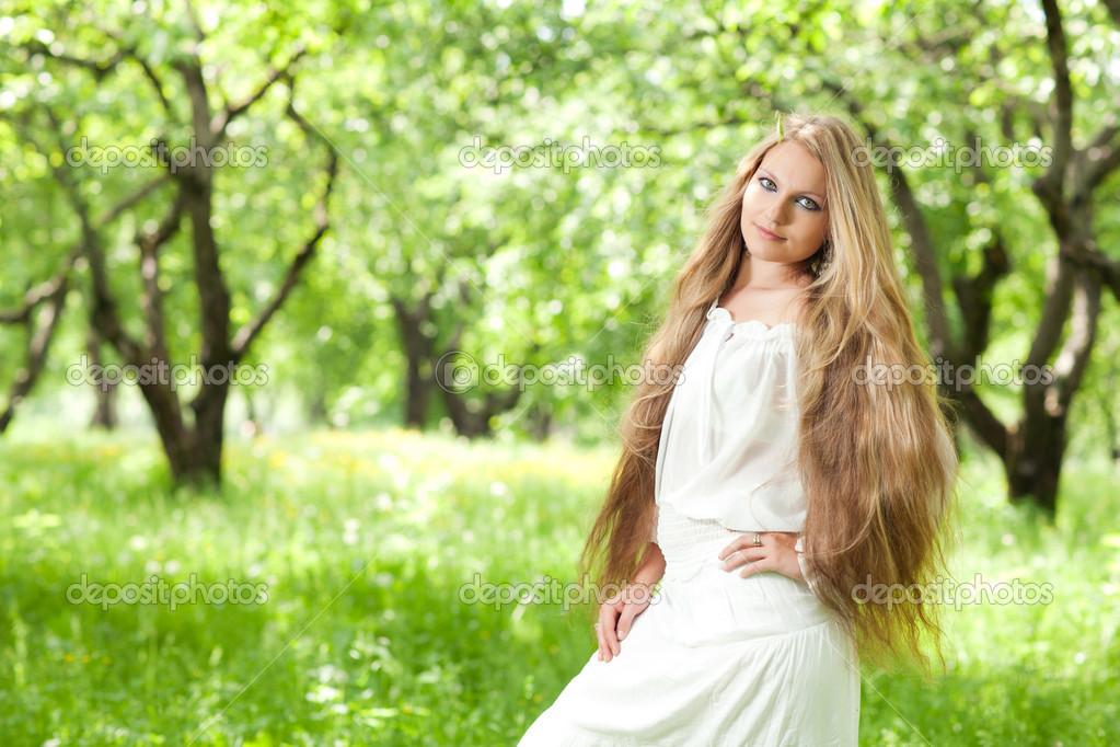 长长的头发和一件白色的连衣裙的漂亮年轻女孩 — 照片作者 melektaus图片