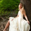 Beautiful bride near the tree — Stock Photo