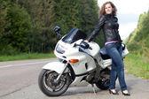 женщина, стоя рядом с мотоциклом — Стоковое фото