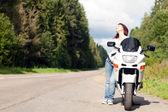 Mujer cerca de una motocicleta — Foto de Stock