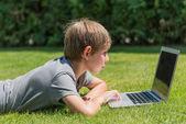 Garçon utilisant l'ordinateur portable à l'extérieur — Photo