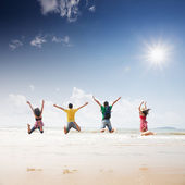 Friends jumping on beach — Stock Photo