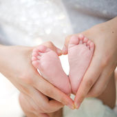 Mother's hand hold baby's foot — Stock Photo