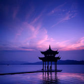 Ancient pavilion on the west lake with sunset in hangzhou,China. — Stock Photo