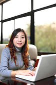 Smiling asian business woman with laptop — Stock Photo