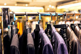 Row of men's suits hanging in closet. — Stock Photo