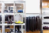 Men's clothes and shoes in modern shop — Stock Photo