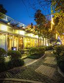 Illuminated restaurant with long footpath — Stock Photo