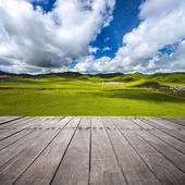Meadows with rolling hills and village — Stock Photo