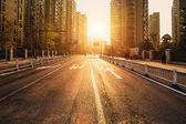 Road and buildings with sunset — Stock Photo