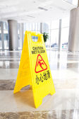 Hallway with a caution sign in English — Stock Photo