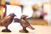 Two copper birds on a table — Stock Photo