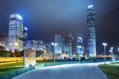 Pathway in the night with modern city background — Stock Photo