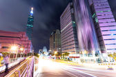 Car light trails and urban landscape in modern city — Stock Photo