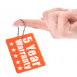 Stock Photo: Hand holding warranty tag