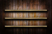 Wooden wall with shelves — Stock Photo