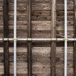 Wooden wall with pipes — Stock Photo
