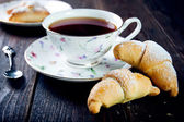 Croissant with jam and tea for breakfast — Stockfoto