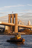 Brooklyn bridge and small ship in new york city — Stock Photo
