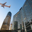 Stock Photo: Airplane on modern city