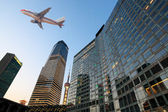 Airplane on the modern city — Stock Photo