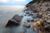 Stones beach at sunset — Stock Photo