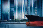 Abstract cityscape of cargo ship with modern buildings — Stock Photo