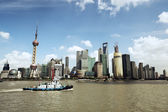 Shanghai skyline and a tugboat — Stock Photo